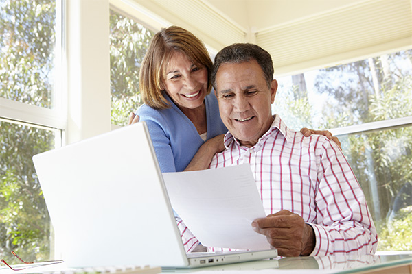 Couple with Paper and Laptop