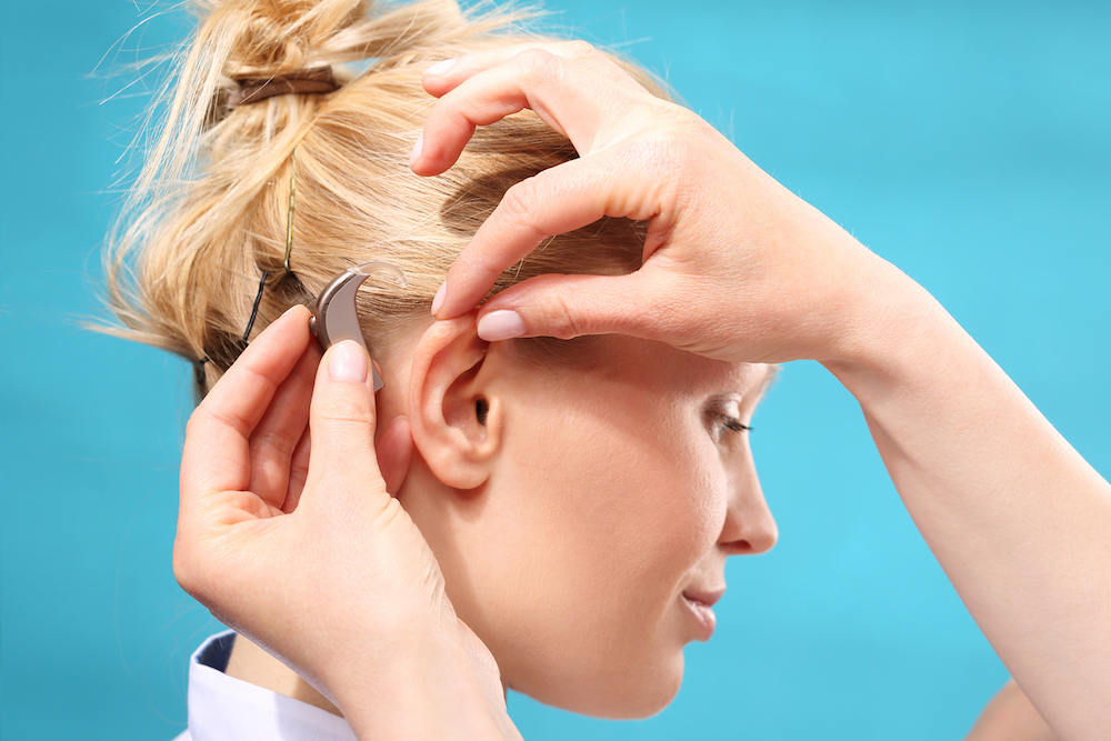 Woman is being fitted for a pair of tinnitus preventing hearing aids.