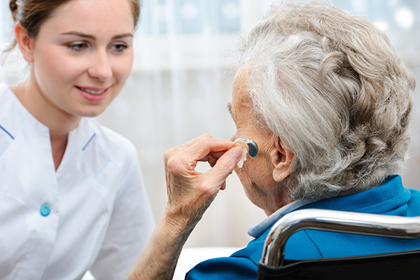 an older woman is wearing hearing aids for the first time