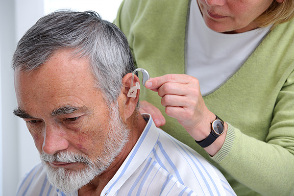 a man being fitted with hearing aids by an audiologist