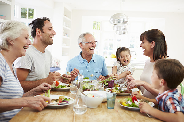 a man with hearing loss is talking with his family over dinner