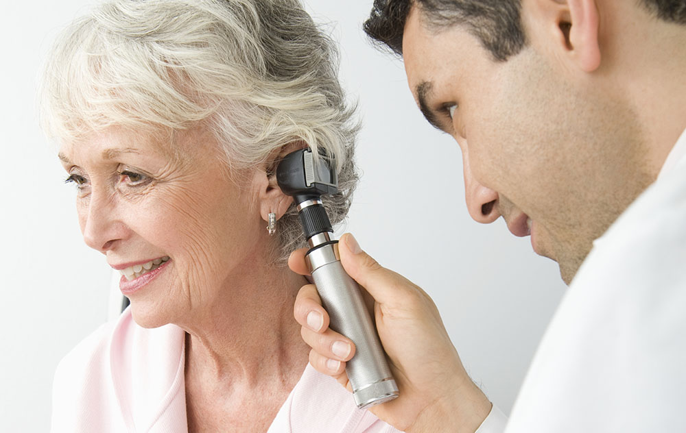 an older woman is getting her hearing checked out