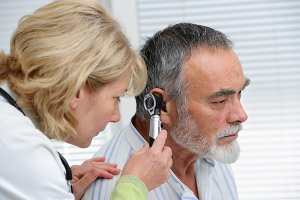 a man having his ear looked at by a hearing specialist