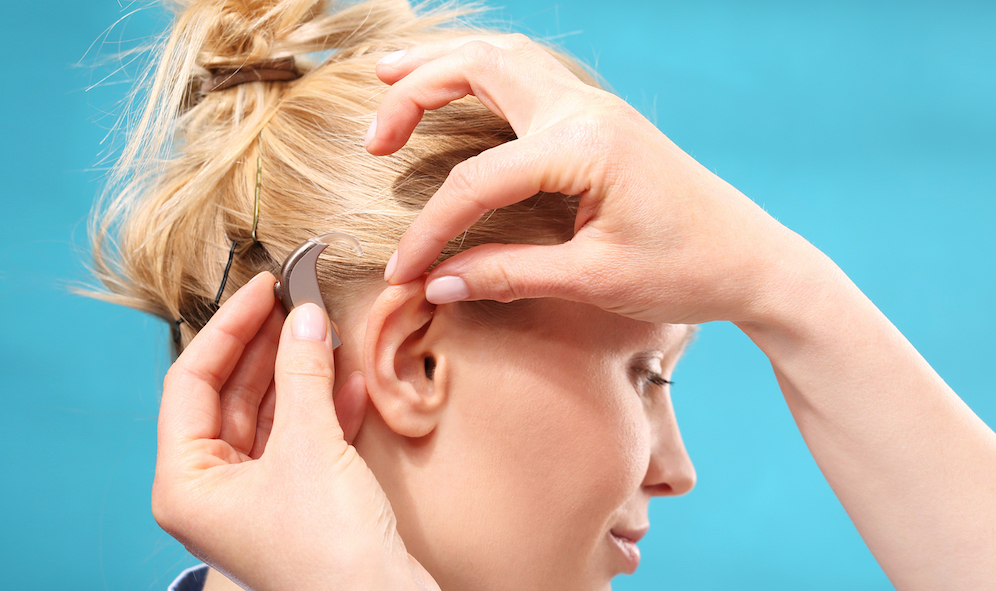 a woman with blond hair is getting fitted for a new hearing device