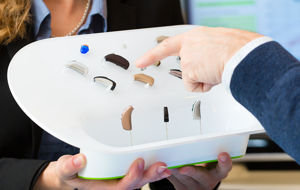 many sets of hearing aids on display with a hand choosing one