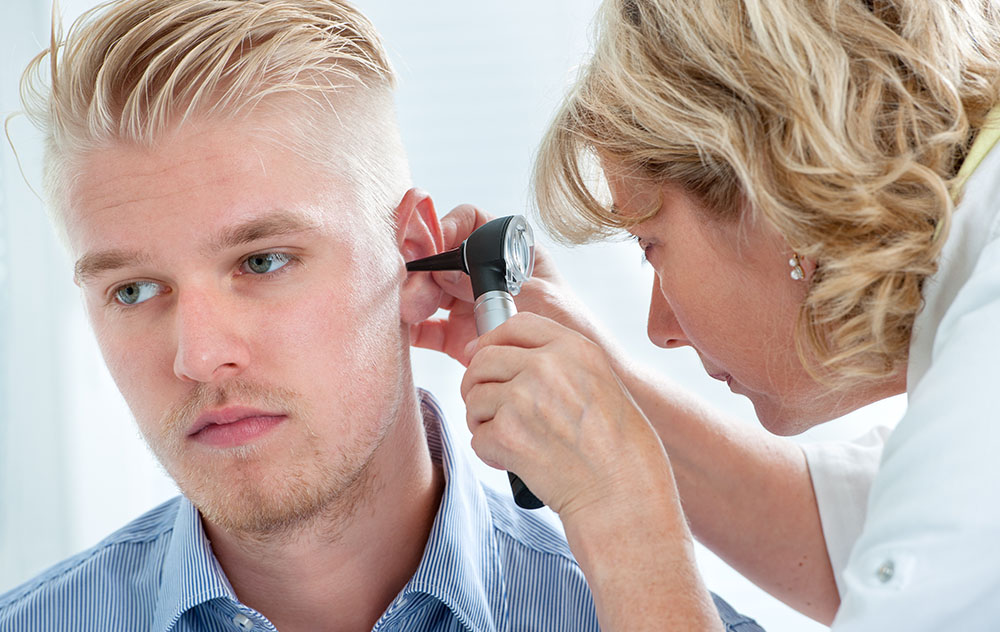 a younger man getting tested for hearing loss