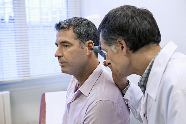 a hearing specialist examining his patient's inner ear for abornmalities