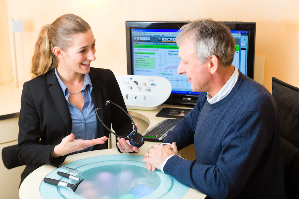a hearing loss patient discussing his audiogram with a smiling hearing professional