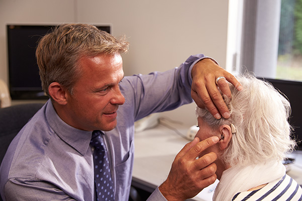 a hearing specialist testing new hearing aids on a patient