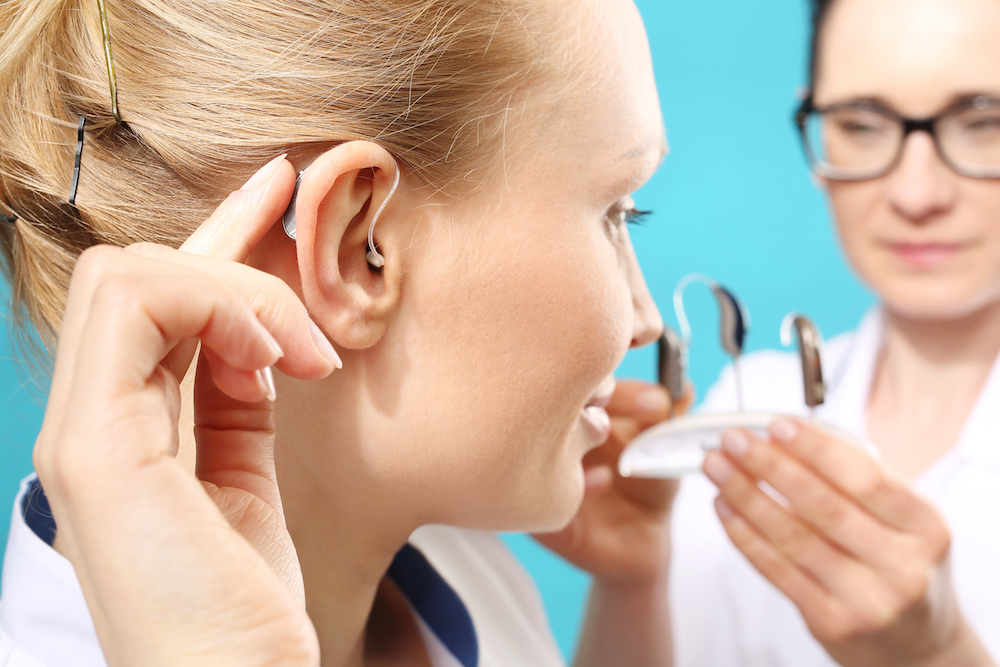 a patient showing off her new hearing aids