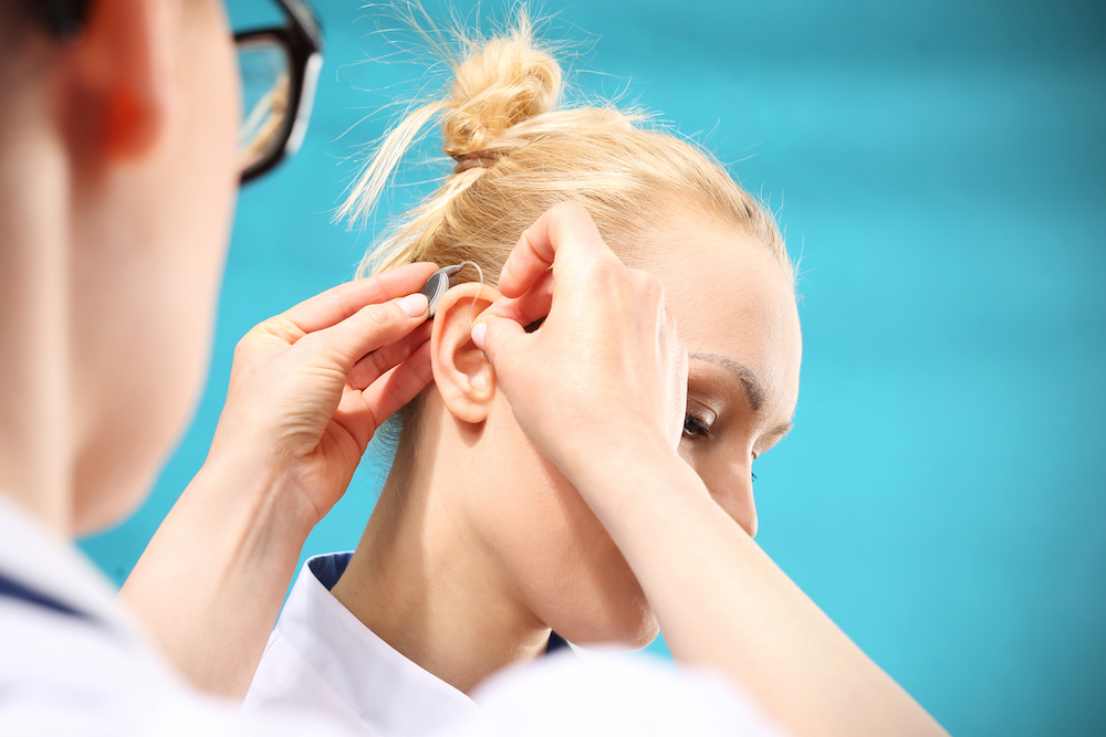 a woman is having a new hearing aid fitted to her ears