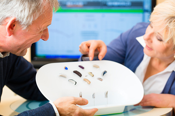two hearing loss patients browsing through a selection of hearing aids