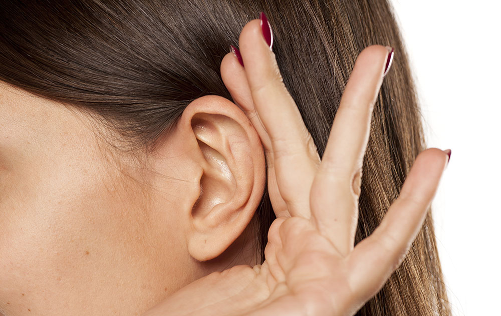 a hand cupped to the ear of a brown haired woman