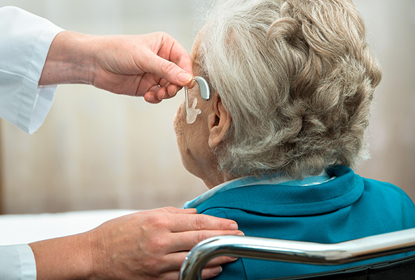 an older hearing loss patient receiving hearing aids
