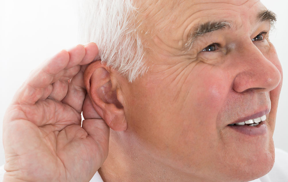 a hearing loss patient holding a hand to his right ear