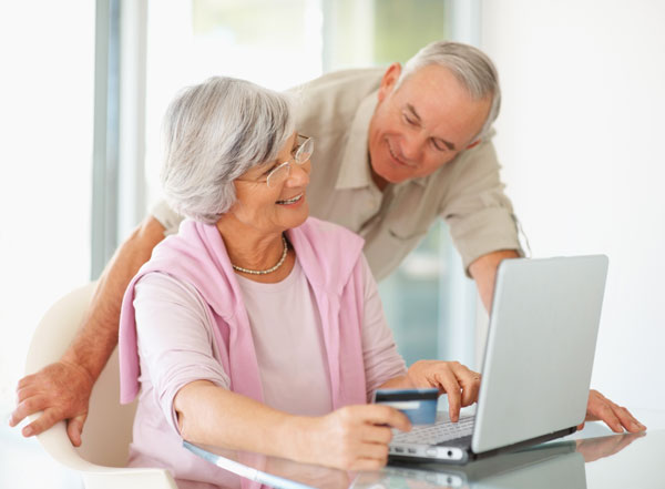 a couple standing over a laptop while researching new hearing aids