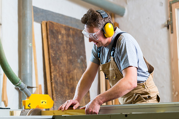a man cutting wood while using proper ear protection